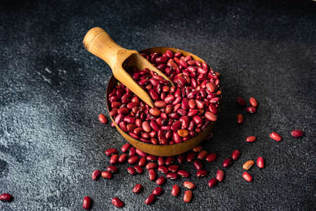 Cooking concept with organic beans in a bowl on dark concrete background with copy space