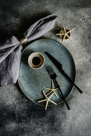 Rustic table setting with grey ceramic plates and black metal cutlery on stone grey textured background with copy space Reklamní fotografie