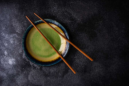 Asian table setting with chopsticks on dark concrete background with copy space