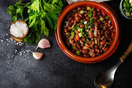 Traditional georgian red beans dish lobio with pomegranate on rustic table with copy space