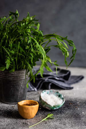 Organic food concept with flax seeds, rocket herb and  sea salt on grey concrete  background