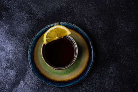 Tea time concept with cup of tea with lemon on dark concrete background with copy space