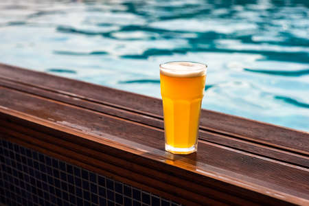 Plain pint glass of cold lager beer sitting on edge of blue swimming pool