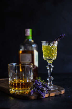 Traditional italian lemon alcohol drink limoncello and wiskey with lavender flowers on dark rusty table