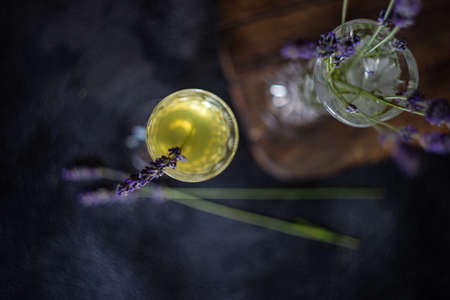 Traditional italian lemon alcohol drink limoncello with lavender flowers on dark rusty table