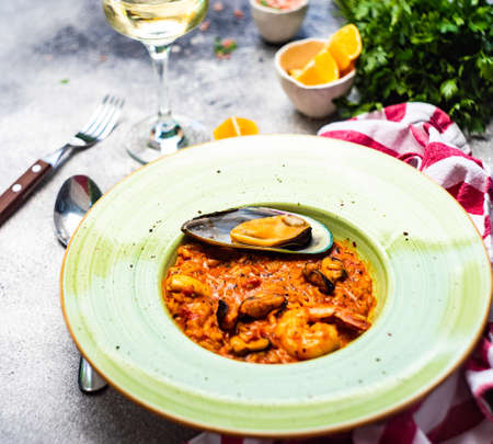 Italian risotto with seafood, served with glass of dry white wine, lemons and salt on concrete background with copy space 免版税图像