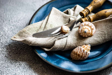 Marine cutlery set with shells and sea stars on grey concrete background with copy space 免版税图像