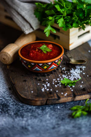 Traditional georgian tomato sauce Satsebeli in ceramic bowl with spices on rusty background with copy space