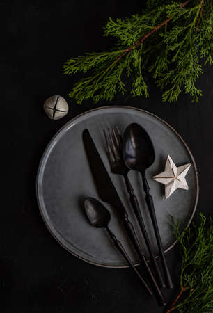 Rustic table setting for festive holiday Christmas dinner with gift box, fir tree and decor on stone background with copy space