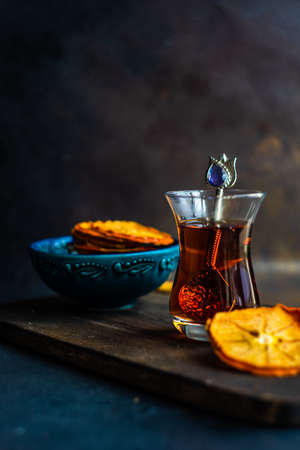 Turkish tea concept with dried persimmons on dark background with copy space