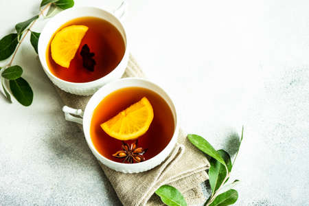Mulled tea with lemon and spices on stone table with copy space