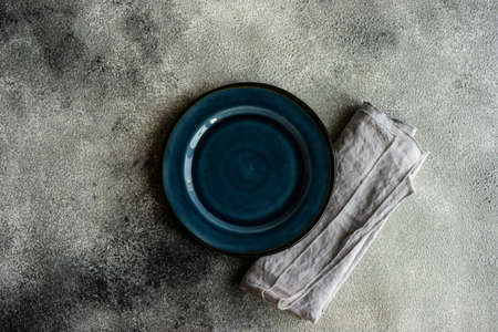 Cutlery set with empty plates on stone background with copy space