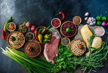 BioGesund mit Bio-Gemüse, Kräutern, rohem Fleisch, Samen und Getreide auf Steinhintergrund mit Kopierraum Standard-Bild