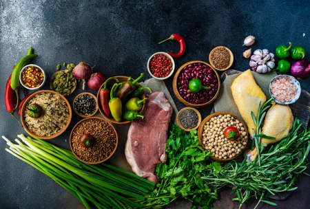 OrganicHealthy with organic vegetables, herbs, raw meat, seeds and cereals on stone background with copy space Stock Photo
