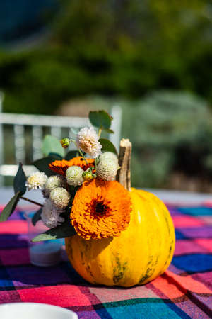 Autumnal table decor with pumpkin like a vase with autumnal flowers Stockfoto