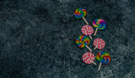 Variety of sugar candies on stone background with copy space