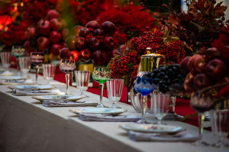Autumnal table setting in red color decorated with red apples and pomegranate Stockfoto
