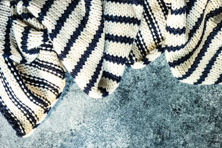 White and blue warm stripped knitted scarf on stone background with copy space