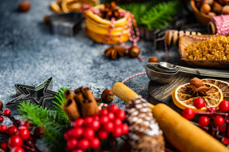 Christmas cooking background with nuts, orange, anise star and cinnamon with decor on  stone background with copy space