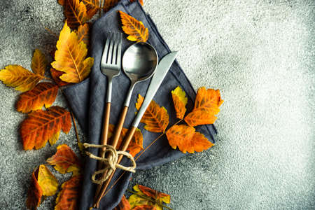 Autumnal table setting with bright yellow leaves and pumpkins on stone background with copy space Stock Photo