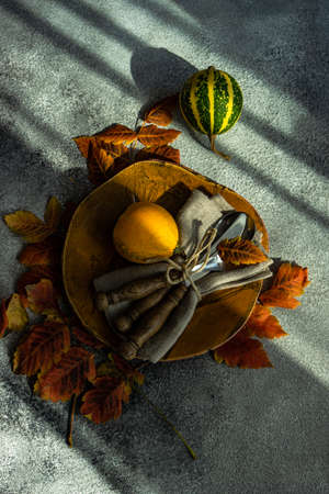 Autumnal table setting with bright yellow leaves and pumpkins on stone background with copy space 写真素材
