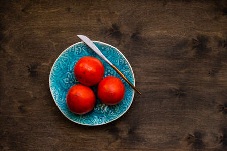 Ripe persimmon as an autumnal dessert on rustic background with copy space Stock Photo