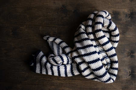 White and black stripped knitted scarf on rustic background with copy space