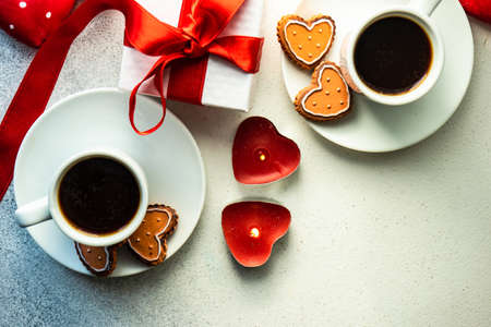 St. Valentine card concept with heart shaped cookies and cup of coffee on stone white background with copy space