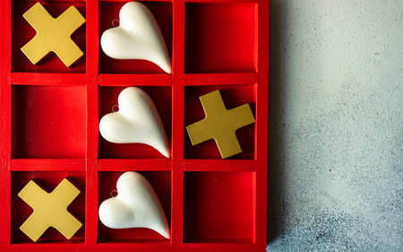 St. Valentine card concept with tic-tac-toe board game and hearts on stone white background with copy space
