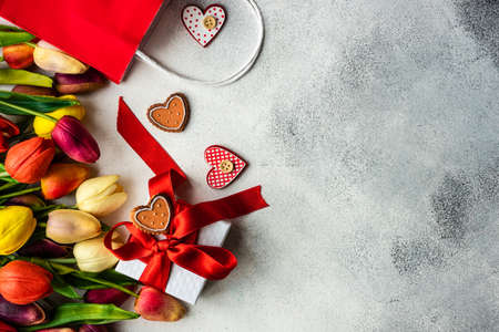 St. Valentine card concept with tulip flowers and gift on stone background with copy space