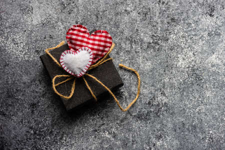 St. Valentine card concept with  gift box and heart on stone background with copy space
