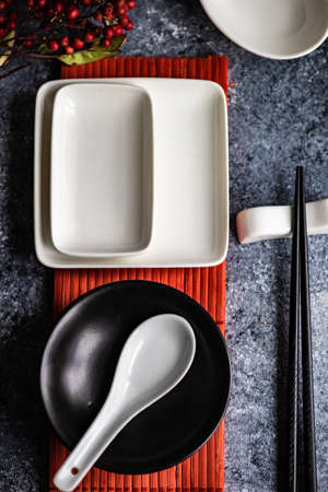 Asian table setting with wooden chopsticks and ceramic bowls on stone background with copy space