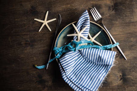 Summer table setting with plates and cutlery decorated with sea stars and shells on stone background with copy space