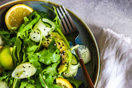 Healthy vegetable salad with aragula,  avocado and sesame seeds on concrete background with copy space