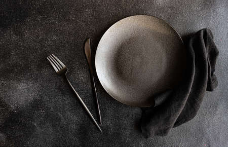 Table setting with plate, napkin and cutlery in black with copy space