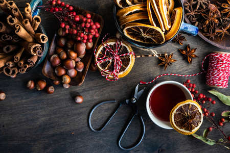 Milled or spiced wine or Gluehwein with oranges, anise star, cinnamon and berries on rustic wooden table with copy space Stock fotó