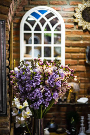Red brick wall with windown and flowers