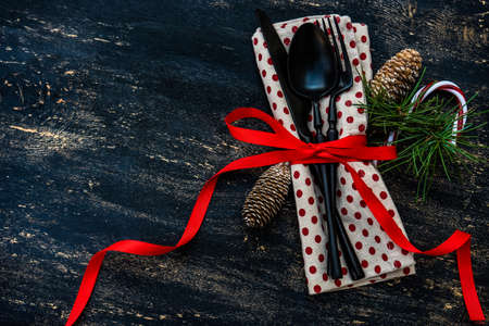 Table setting on vintage and rustic wooden background with cutkery decorated with ribbon