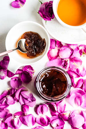 Tea time concept with cup of tea and rose petal jam served on a stone table with copy space
