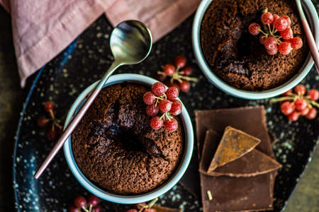 Fresh bakes chocolate fondant cake with red Shepherdia argentea berries served in a bowl Stock Photo