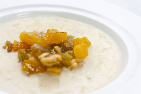 milk porridge with fruit, walnuts and butter in a white plate close-up