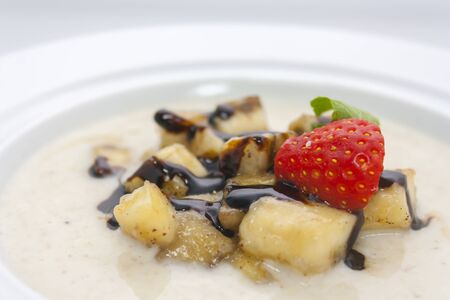 milk porridge with bananas, strawberries, chocolate sauce and mint in a white plate close-up