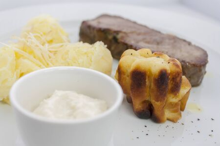yorkshire pudding and roast beef with mashed potatoes and sour cream sauce on a white plate