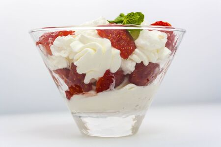juicy strawberries with cream and a sprig of mint in a transparent glass bowl on a white background side view Stok Fotoğraf