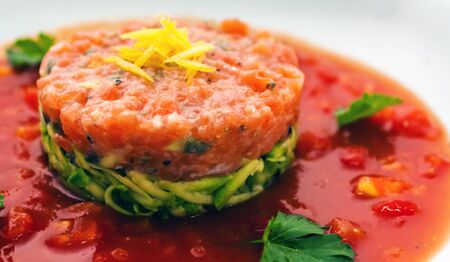 Tartar beefsteak with fresh cucumbers, olives and tomato sauce in a white plate close-up Stock Photo