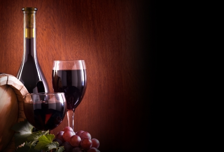 still life: Red wine glass, barell and bottle on a wooden background. Stock Photo