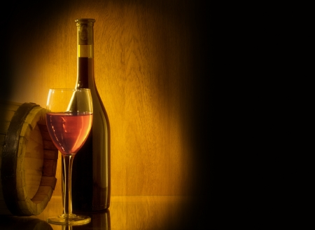 lowkey: Red wine glass, barell and bottle on a wooden background. Low key still life.