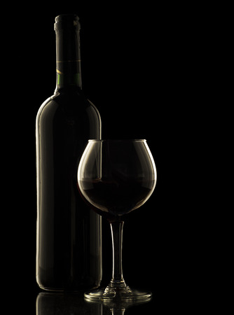 Red wine bottle and glass on black background. Stock Photo
