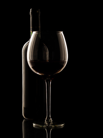 Red wine bottle and glass on black background. photo