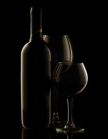Red wine bottle and glasses on dark background. photo